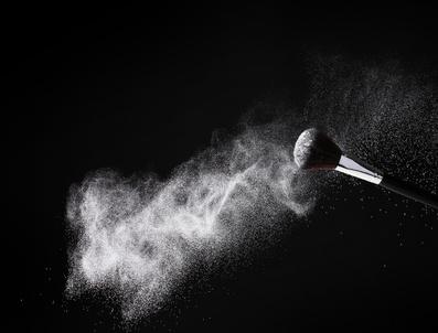 Make up brush with powder isolated on black