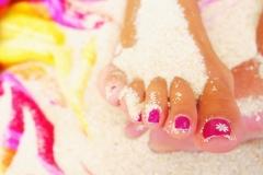 piedi con unghie curate sulla sabbia